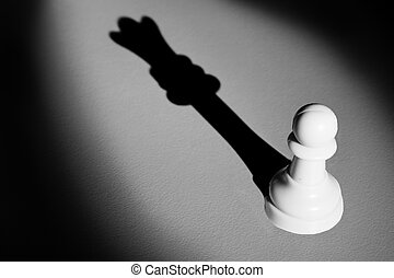 Chess pawn standing in a spotlight that make a shadow of queen with darkness actistic conversion