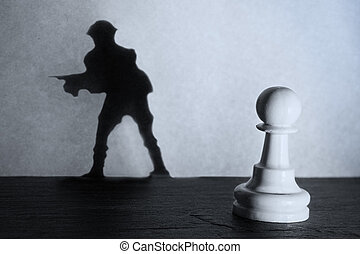 Chess pawn standing in a spotlight that make a shadow of soldier with darkness actistic conversion