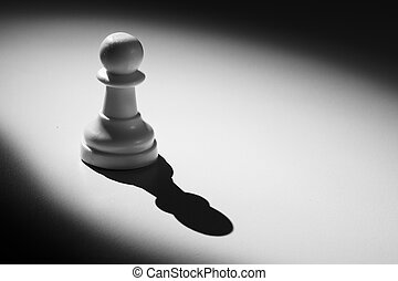 Chess pawn standing in a spotlight that make a shadow
