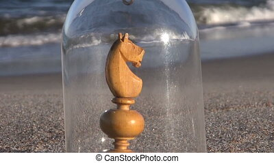 Chess piece in glass case on beach - Wooden handmade crude...