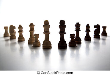 chess pieces lined up in a row on a gray close up