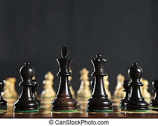 Chess pieces on board - Close up of chess pieces on wooden...