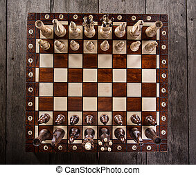 Chess pieces on old wooden table.