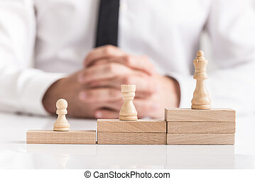 Chess pieces on stacked stepped wooden blocks