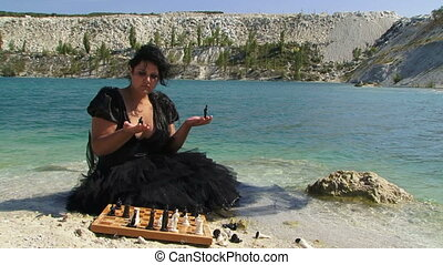 Chess queen - Woman in black playing with chess pieces
