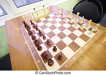 Chess stand on chessboard in room of chess club; brown and white wooden figures