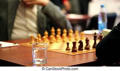 Chess starting position on board closeup, glass of water in...