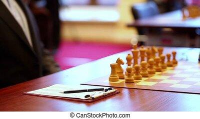 Chess starting position on board closeup, man take pen, ...