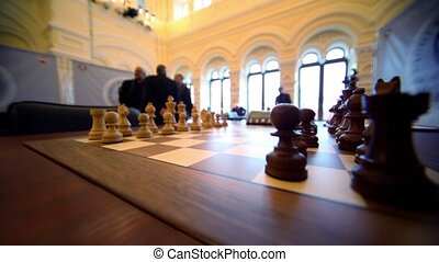Chess starting position on board closeup, people walk at...