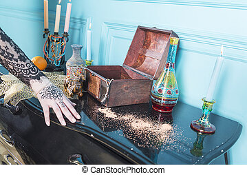 Chest, candles and a bottle on the table.