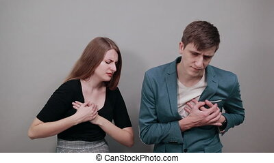 Chest pain can have a variety of causes, heart attack, major health. Young attractive couple boyfriend girlfriend two people, dressed black t-shirt, blue jacket, grey background