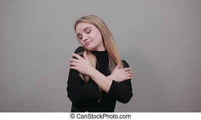 Chest pain can have a variety of causes, heart attack, major health. Young attractive woman, dressed black sweater with green eyes, blonde hair, background