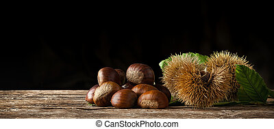 Chestnuts and chestnut bur on wooden table. - Chestnuts and...