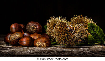 Chestnuts and chestnut bur on wooden table. Light painting...