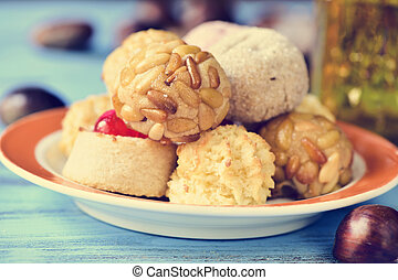 a plate with some different panellets, typical pastries of Catalonia, Spain, eaten in All Saints Day, and some chestnuts on a blue rustic wooden table