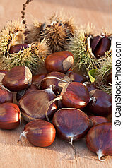 Chestnuts - Brown chestnuts on a wooden desk.