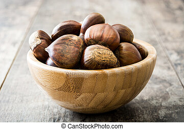 Chestnuts in a bowl on wooden background