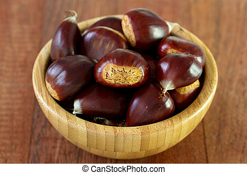 chestnuts in bowl on brown background