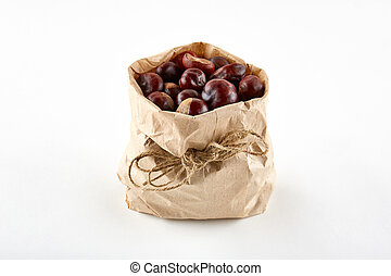 Chestnuts in paper bag on white background