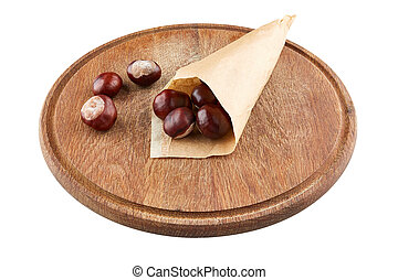 Chestnuts in paper package on wooden plate. Isolated on white background