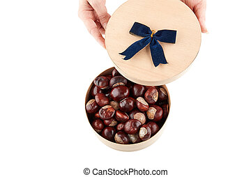 Chestnuts in round wooden box. Isolated on white background