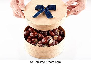Chestnuts in round wooden box on white background