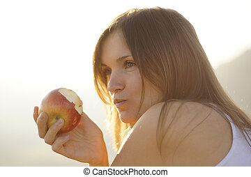 Beautiful young woman eating a red apple in bight sun