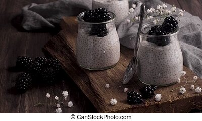Chia pudding with blackberries, three portions in glass jars on a dark table.