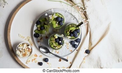Chia pudding with kiwi, blueberries and coconut slices, three portions in glass jars on a white table.