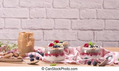 Chia pudding with oat and berries in a glass jar on rustic ...