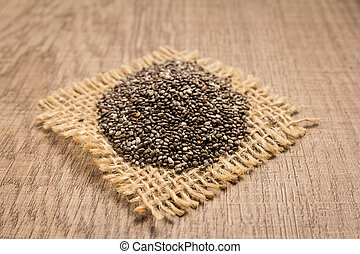 Chia Seed. Grains on square cutout of jute. Wooden table. Selective focus.