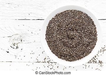 Chia seeds in bowl on white wooden background. Top view