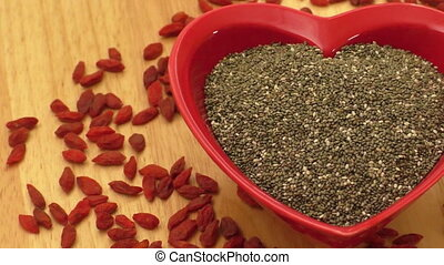 Chia seeds in heart shaped ceramic bowl and dried goji berries