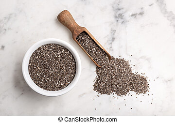 Chia seeds in wooden scoop and bowl on marble table. Salvia hispanica. Copy space, top view