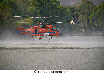 CHIANG MAI, THAILAND - APRIL 4, 2020: Unidentified helicopter from Department of Disaster Prevention and Mitigation. Ministry of Interior Thailand? carrying water to pour the wildfire in Doi Suthep Mountain in Chiang Mai, Thailand