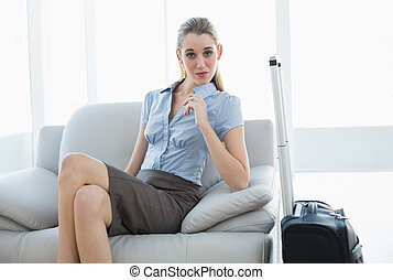 Chic businesswoman posing sitting on couch nest to her suitcase