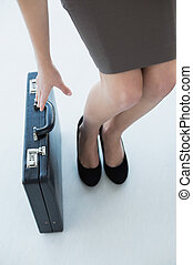 Chic businesswoman reaching for her black briefcase