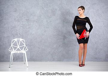 Slender elegant woman in a black dress with transparent stripes holding an envelope handbag