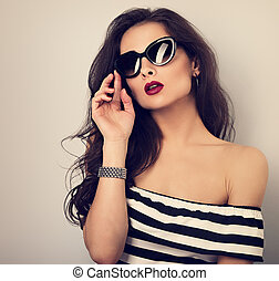 Chic female model with long hair posing in fashion sunglasses in striped dress with hand near face. Toned closeup portrait