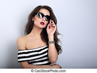 Chic female model with long hair posing in fashion sunglasses in striped dress with hand near face on blue background