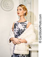 e1c8120a9 Elegant young woman in evening dress and mink fur jacket posing in vintage  interior. Jewellery. Fashion shot.