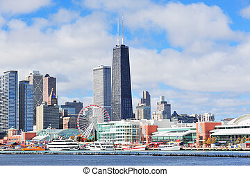 Chicago city downtown urban skyline with skyscrapers over Lake Michigan with cloudy blue sky.