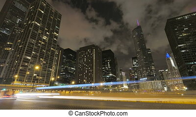 Chicago Skyscrapers at Night with Traffic Crossing the City. Video timelapse of Chicago downtown skyscrapers with cars driving at full speed on its streets. Awesome Chicago city center skyline at night in the United States of America. Illuminated skyscrapers of Chicago in a cloudy night. Trump Tower...