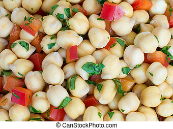 Chick-pea background, with pieces of red bell pepper and chopped parsley