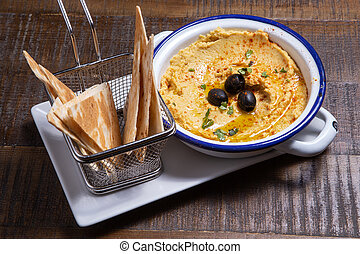 A bowl of creamy chick pea hummus with olive oil and pita chips.