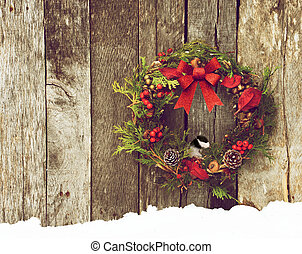 Chickadee perched on a wreath.