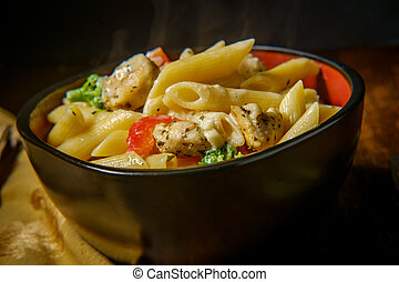 Grilled chicken alfredo penne primavera with dark moody lighting on rustic wooden kitchen table