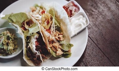 Chicken and cheese and beef tacos served with guacamole, ...