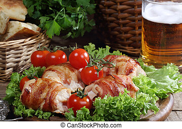 Chicken beaters in bacon submitted on leaves of salad with fresh tomatoes and beer in a transparent mug