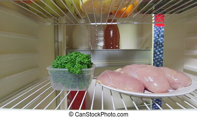 Woman takes out chicken breast and parsley from the fridge, inside view